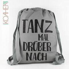 grauer Rucksack mit Spruch TANZ MAL DRÜBER NACH schwarz Glitzer