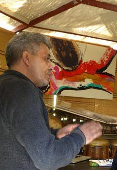 Un homme marocain et un tableau avec peintures vives en fond