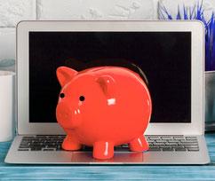 Laptop vor einer weißen Wand mit einem roten Sparschwein