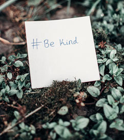 A note saying Be Kind, on a nature background