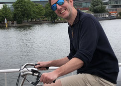 smiling cyclist on a bridge