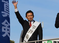 市長選挙で選挙カーに乗って演説する