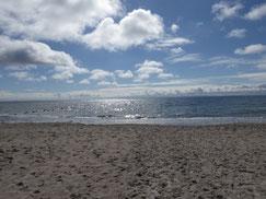 Hellbrauner Sandstrand vor blauem Meer. Am Himmel lugt die Sonne durch weiße Wolken