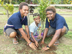 OISCA trainees support students when planting tree