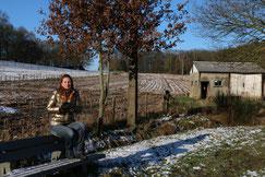 Winterlandschap met op de helling een bos en op de voorgrond een vrouw zittend op een bank. Een beschutting voor vee op de rechterkant.