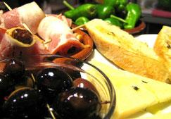 Verschiedene Tapas: Oliven, Datteln im Speckmantel, Pimientos de Padrón, Manchego-Käse