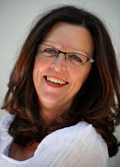 Porträtfoto von Sybille mit weißer Bluse. Sybille schaut strahlend ins Bild.