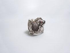 Une bague en argent avec une pierre transparente est posée sur un fond blanc.