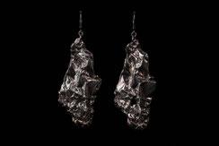 De grosses boucles d'oreilles en argent froissé sont exposées sur fond noir.
