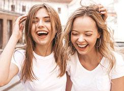 Zwei junge Frauen laufen Arm in Arm und lachen ausgelassen