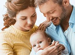 Junge Eltern halten ihr Baby auf dem Arm und schauen lächelnd auf das Kind hinunter
