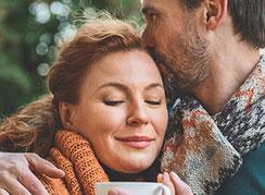 Paar mittleren Alters, der Mann hat einen Arm um die Frau gelegt, die Frau lächelt mit geschlossenen Augen