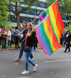 Eine Frau und ein Mann tragen jeweils eine Regenbogenfahne beim CSD Berlin. Foto: Helga Karl