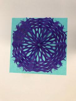 Een uit paarse vloeipapier geknipt kleedje op een aquablauwe ondergrond