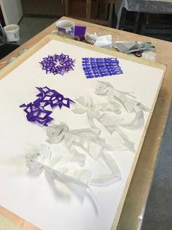 Op een vel wit papier liggen verschillende paars en blauw geknipte papieren kleedjes, en een witte slinger van poppetjes.