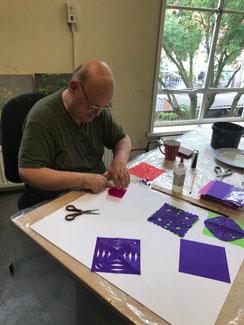 Een man is een velletje rood vloeipapier aan het dubbelvouwen omdaar na in de randen te gaan knippen om er een kleedje van te maken met een gaatjespatroon