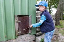 Kind öffnet Stalltür