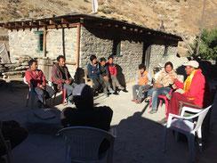 Versammlung mit Lama, Ziegenhirten und Dorfbevölkerung