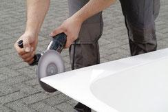 Die Schnittkanten des Wanneneinsatzes werden gründlich mit einem Exzenter-Schleifer bearbeitet.