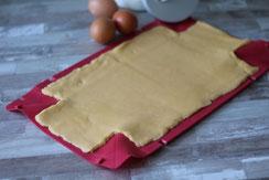 Schritt 1: Die Zutaten für den Teig vermischen und ihn auf der offenen Form ausrollen. Die Ecken ausschneiden.