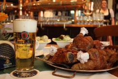 Ein typisch bayerisches Gericht bestehen aus ofenfrischer Ente, Knödeln, Salat und Bier steht im Wirtshaus Paulaner im Tal