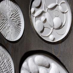 Ronds de faïence blanche sculptés et collés sur du bois