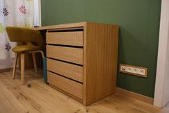 Prises de courant et multimédia de la collection DECENTE. Le cadre de finition en bois s'associe parfaitement avec ce bureau au style scandinave. D'autant plus lorsqu'il est installé sur un mur verts foncé.