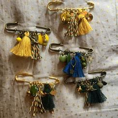 Broches dorées ou bronze constituées de pompons et breloques jaune, vertes, et bleu