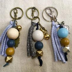 Porte clés constitués de grosses perles de bois naturel, ivoire, perles forme hexagonales dorées avec des pompons de rubans spaghettis gris motif pois, pompons liens de cuir ou pompons de liens irisées colorés