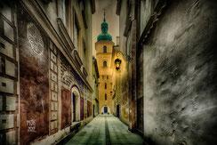 Mit Laterne beleuchtete Gasse zur Heilig Kreuz Kirche in Warschau
