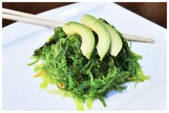 Salade d'algues et tranche d'avocat sur une assiette blanche et baguettes japonaises