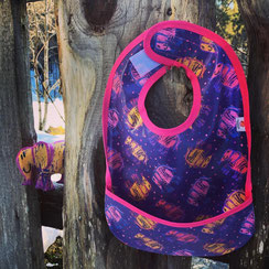 """Bib with the motif """"elephant's universe"""" and the soft toy version of the messy little elephant peeking at the bib"""