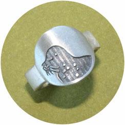 Bild:Ring mit Robbe,Oberteil ist eine runde Platte auf der ist die Robbe vertieft eingearbeitet und dunkel gemacht,der Ring verläuft nach unten hin schmaler