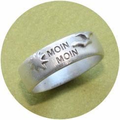 Bild: schmaler Ring mit Moin Moin Schriftzug einer Sonne und zwei Möwen