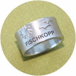 Ring: breiter Silberring mit Möwen und Sonne erhaben aufgelötet und einem Schriftzug Fischkopp ind dunkel vertieft graviert