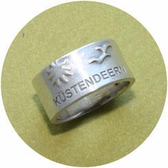 breiter Ring mit Schriftzug Küstendeern, einer Sonne und zwei Möwen
