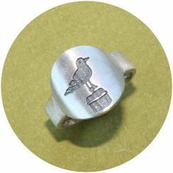 Bild:Ring mit Möwe,der Ring hat oben eine runde Platte auf der ist die Möwe auf dem Poller vertieft eingearbeitet und dunkel gemacht,der Ring wird nach unten schmaler.