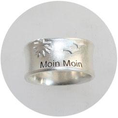 Bild: Moin Moin Ring, es ist ein breiter Silberring mit Sonne und zwei kleinen Möwen,es ist ein vertiefter Schriftzug mit Moin Moin eingearbeitet und dunkel gemacht,Schmuck aus Flensburg von Andrea Hildebrandt