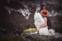 Halterin mit Hut sitzt mit Samojede auf einem Felsen vor einer Bergkulisse fotografiert von der Ostschweizer Hundefotografin Monkeyjolie