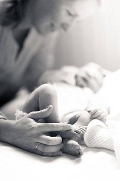 Newborn Fotoshooting Mutter hält Kind und streicht über den kleinen Fuss fotografiert von der Schweizer Familien Fotografin Monkeyjolie