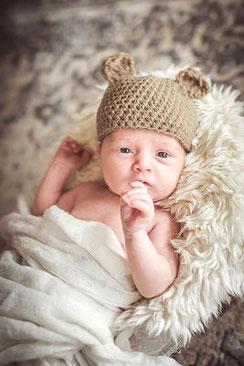 Newborn Fotoshooting  Baby liegt auf einem Fell mit einer Strickmütze mit Ohren schaut in die Kamera fotografiert von der Schweizer Familien Fotografin Monkeyjolie