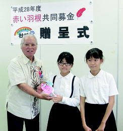 富野小中学校児童会から那根会長へ募金が贈呈された=18日、市社協(石垣市共同募金委員会提供写真)