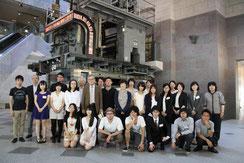 日本新聞博物館ロビーの輪転機前で記念撮影