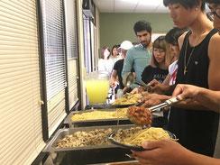 学生達が列に並んで料理をよそう様子