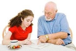 Senior mit junger Frau am Tisch