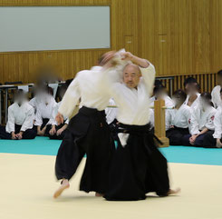 画像1:右足を軸とし、右手を額に振りかぶって結び左足を非軸足として前方(壁の方向)に回転し(右足は袴の下で内股になっている)