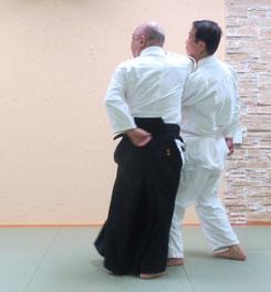 画像②右手は同側の側頸に降りて肘は受けの中丹田に密着、体側の非軸足は内股に踏み換えて軸とするところ。右半身入り身転換で画像③へ。