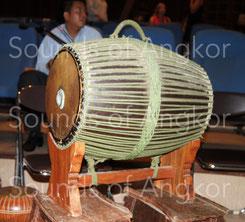 Tambour en tonneau skor sampho sur support. On remarquera le dispositif d'accordage rapide au centre de la peau. Le Blu-tack remplace aujourd'hui la traditionnelle pâte de riz. Cambodge.
