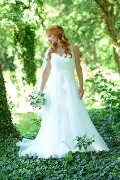 Porträt einer Braut mit langen rötlichen Haaren, langem weißen Schleier in einem weißen Hochzeitskleid mit Blumenstrauß.