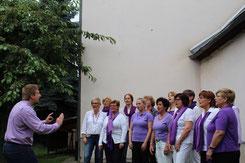 """Probe im Bosenheimer Kirchgarten: Chorleiter Christian Baer (links) arrangiert den Chor """"Klanglicht"""" seit rund fünf Jahren. Foto: M. Ristow"""
